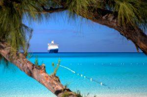 A ship waits on the horizon on a beautiful beach in the Caribbean.