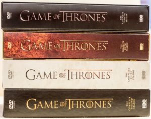 London, UK - June 14, 2016: A studio shot on a white background of the fantasy drama series Game of Thrones DVD boxset featuring four of the first five seasons. All the books were written by George RR Martin while the series was created by David Benioff and DB Weiss and produced by HBO.